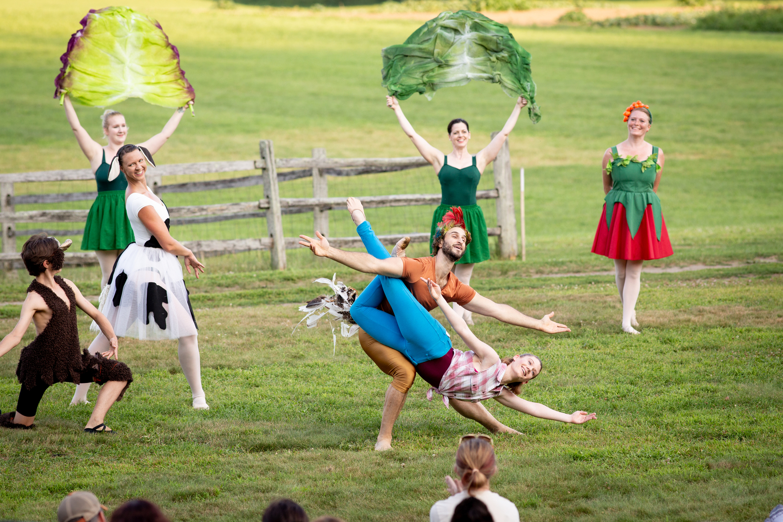 Ballet dancers on a farm doing a fish dive during a performance of the Farm to Ballet Project