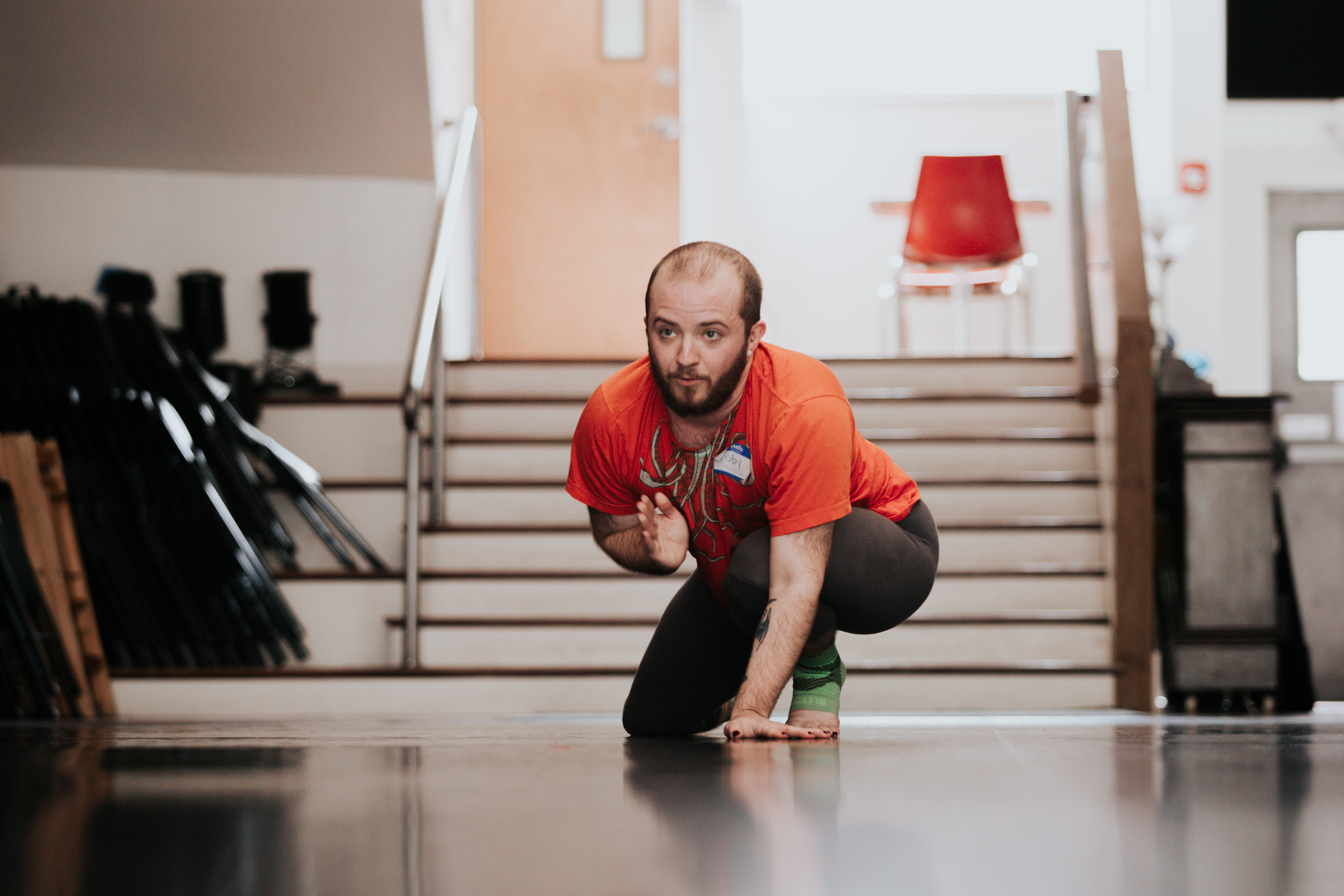 Person crouching low with one hand pointing forward. Orange t-shirt. Black pants. Stairs behind their body.