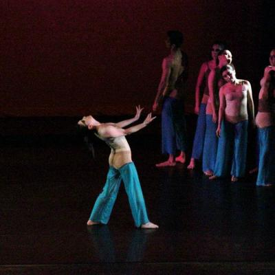 Ensemble of dancers on stage wearing tan with tortoise legs. Soloist standing mid-stage with arms out and head up.